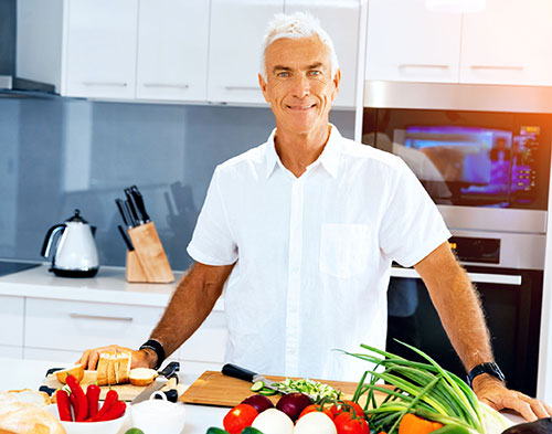 A man in the kitchen cooking with a variety of vegetables in front of him